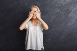 Scared woman covering eyes with hands, see no evil