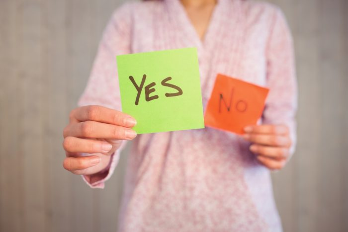 Woman holding yes and no cards on wooden planks background